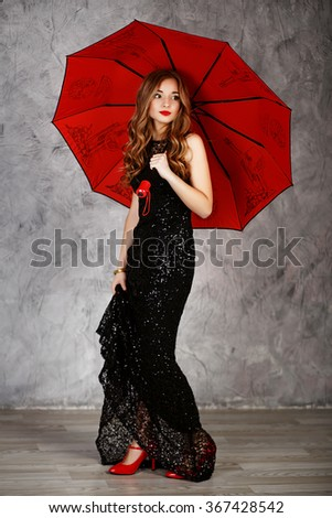 full-length Portrait of a beautiful long-haired young girl in black evening dress with a red umbrella. Young woman with red umbrella - stock photo