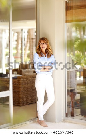 Full length portrait of a beautiful mature woman standing with arms crossed by her living room glass door while looking out.