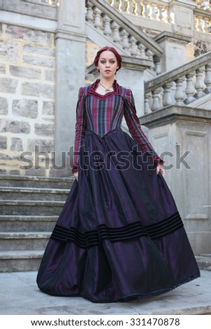 Full Length Portrait Of A Beautiful Red Haired Girl Wearing Gothic Inspired Victorian Era Clothes