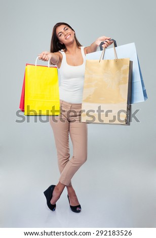 Full length portrait of a beautiful smiling woman holding shopping bags over gray background. Looking at camera - stock photo