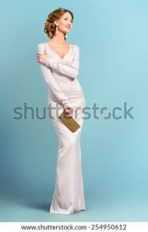 Full length portrait of a beautiful woman in elegant evening dress posing over gray background. Fashion shot. Hairstyle. - stock photo