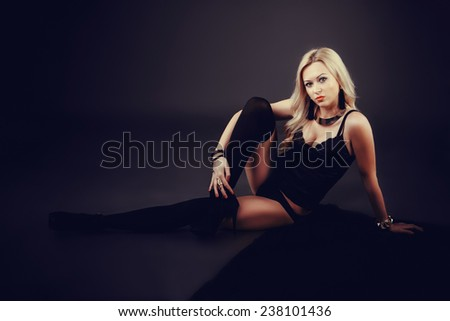 Full length portrait of a beautiful woman wearing lingerie while laying on the floor