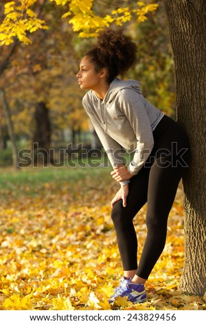 Full length portrait of a beautiful young woman standing in park resting after work out - stock photo