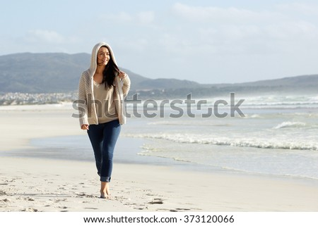 Full length portrait of a beautiful young woman walking on the beach - stock photo