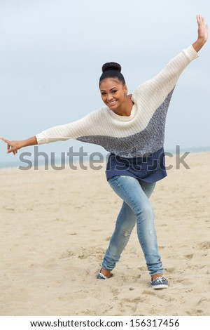 Full length portrait of a beautiful young woman with cheerful expression walking on beach with arms outstretched - stock photo