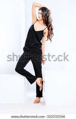 Full length portrait of a beautiful young woman with long brunette hair over white background. Fashion style photo. - stock photo