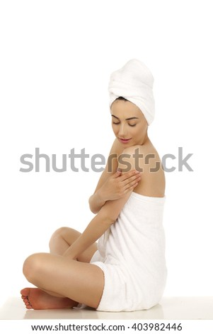 Full length portrait of a beautiful young woman wrapped towel isolated on white background - stock photo