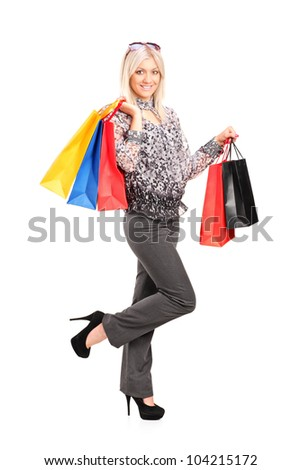 Full length portrait of a blond female posing with shopping bags isolated against white background - stock photo