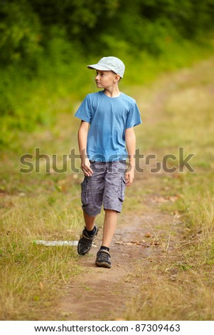 Full length portrait of a boy walking outdoor in a forest - stock photo