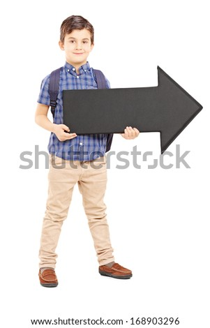 Full length portrait of a boy with school bag holding a big black arrow pointing right, isolated on white background
