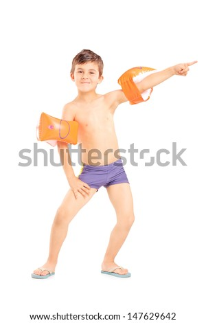 Full length portrait of a boy with swimming arm bands pointing isolated on white background - stock photo