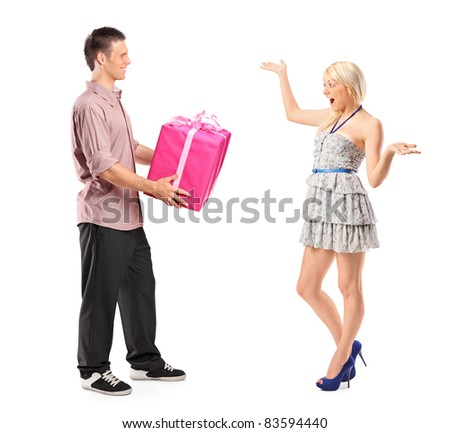 Full length portrait of a boyfriend holding a gift and his excited girlfriend isolated on white background
