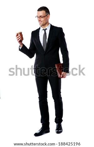 Full-length portrait of a businessman holding cup of coffee and tablet computer over white background - stock photo