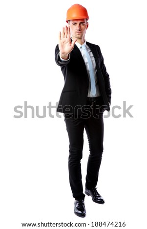 Full-length portrait of a businessman in helmet showing stop gesture over white background - stock photo