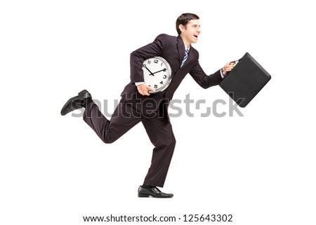 Full length portrait of a businessman running with clock and briefcase isolated on white background