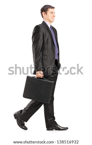 Full length portrait of a businessman walking and holding a briefcase, isolated on white background - stock photo