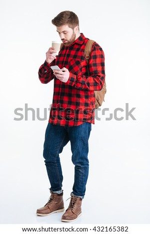 Full length portrait of a casual man drinking coffee and using smartphone isolated on a white background - stock photo
