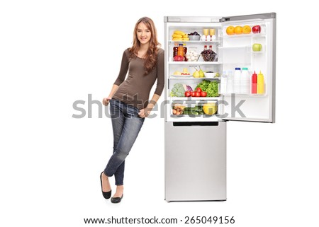 Full length portrait of a casual young girl leaning on an opened refrigerator full of food isolated on white background - stock photo