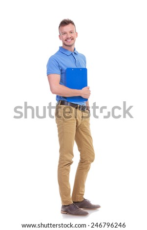 full length portrait of a casual young man holding a clipboard and a hand in his pocket while smiling for the camera. on a white background - stock photo