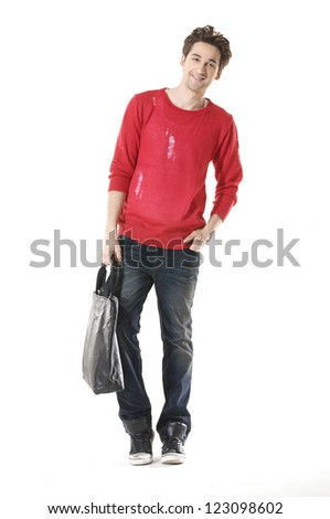 Full length portrait of a casual young man holding bag - stock photo