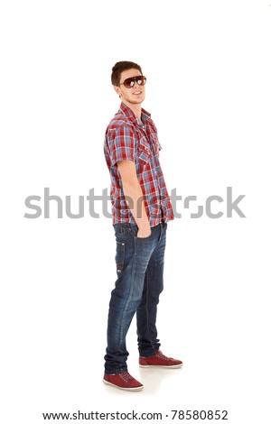 Full length portrait of a casual young man standing with hands in pockets over white background