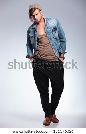 full length portrait of a casual young man with his hands in his pockets looking at the camera. on gray studio background - stock photo