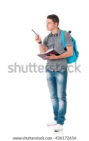 Full length portrait of a caucasian guy carrying some books and a backpack, isolated on white background. Smart  student of college or university writes in a notebook lecture. - stock photo
