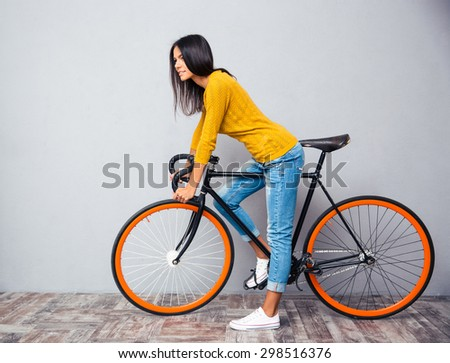 Full length portrait of a charming woman with bicycle on gray background. Looking at camera - stock photo