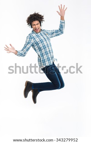 Full length portrait of a cheerful afro american man in headphones jumping isolated on a white background - stock photo