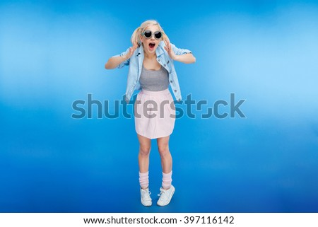 Full length portrait of a cheerful attractive woman looking at camera over blue background - stock photo