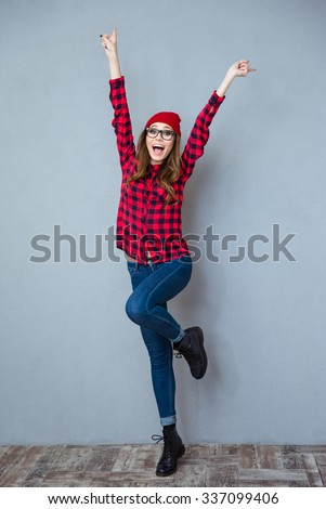Full length portrait of a cheerful casual woman posing with raised hands up on gray background - stock photo