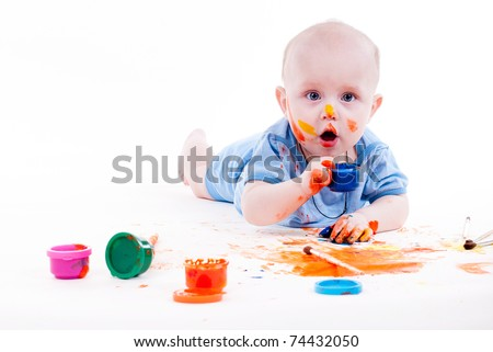 Full-length portrait of a cheerful grimy kid. playing with paint. on a white studio background. - stock photo