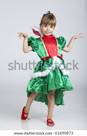 Full length portrait of a cheerful little girl wearing green dress on Saint Patrick's Day, studio image