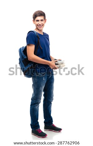 Full length portrait of a cheerful male student with backpack holding books isolated on a white background. Looking at camera - stock photo
