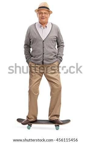 Full length portrait of a cheerful senor standing on a skateboard isolated on white background