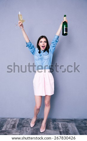 Full length portrait of a cheerful woman holding two glass and bottle of champagne. Looking at camera - stock photo