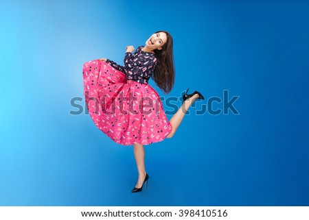 Full length portrait of a cheerful woman in dress posing over blue background - stock photo