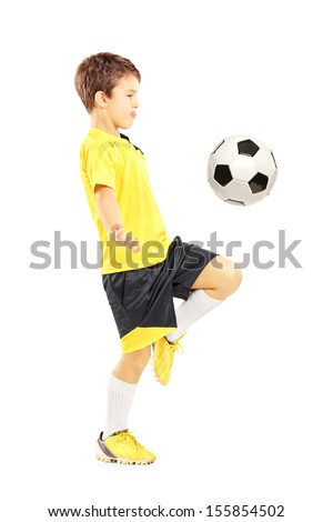 Full length portrait of a child in sportswear joggling with a soccer ball isolated on white background - stock photo