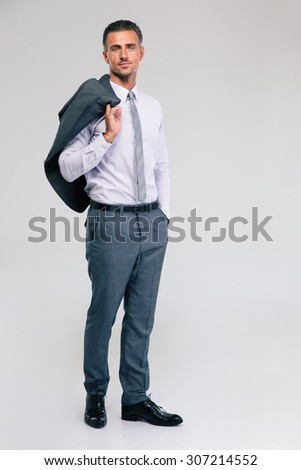 Full length portrait of a confident businessman standing with jacket on shoulder isolated on a white background - stock photo