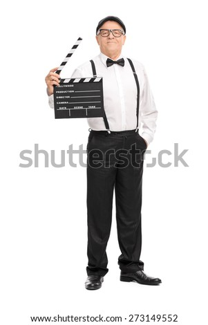 Full length portrait of a confident mature movie director holding a clapperboard and looking at the camera isolated on white background - stock photo