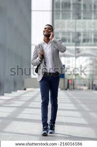Full length portrait of a cool guy walking and talking with cellphone - stock photo