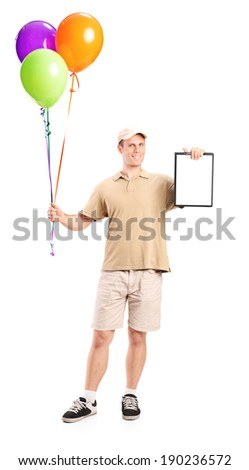 Full length portrait of a delivery boy holding balloons and a clipboard isolated on white background - stock photo