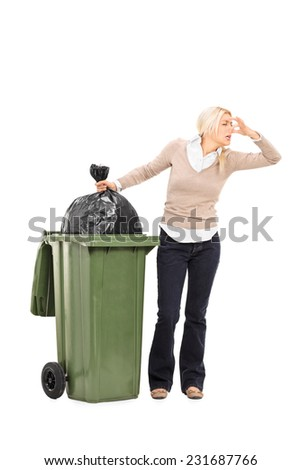 Full length portrait of a disgusted woman standing next to a trash can isolated on white background - stock photo