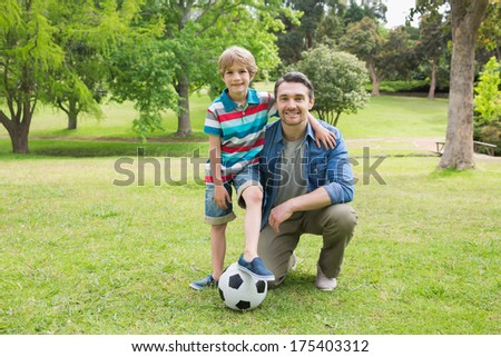 Full length portrait of a father and son with ball at the park - stock photo