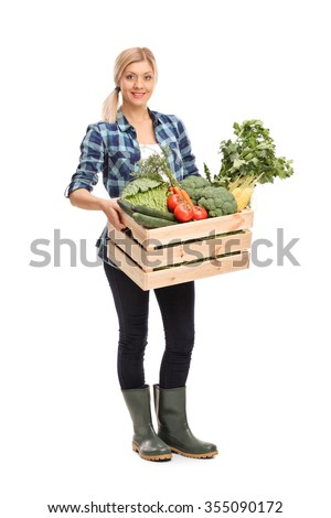 Full length portrait of a female agricultural worker holding a crate full of fresh organic vegetables and looking at the camera isolated on white background - stock photo