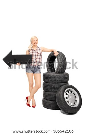 Full length portrait of a female mechanic holding a big black arrow pointing left and leaning on a stack of car tires isolated on white background - stock photo