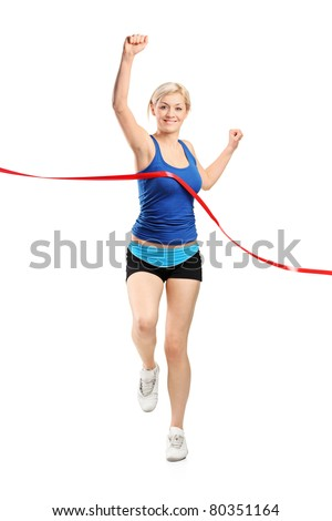 Full length portrait of a female runner running towards a finish line isolated against white background - stock photo