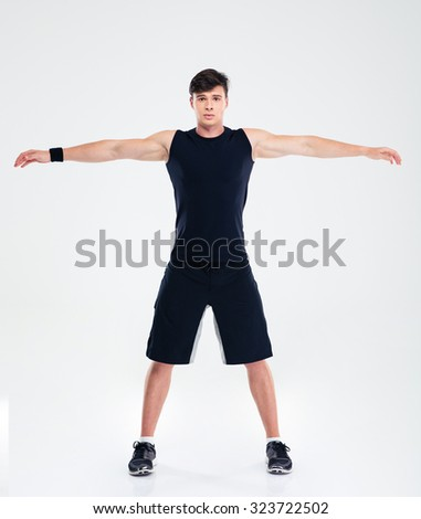 Full length portrait of a fitness man doing warm up exercises isolated on a white background - stock photo
