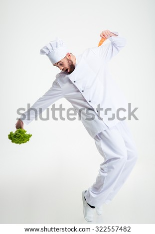 Full length portrait of a funny chef cook holding vegetables and dancing isolated on a white background - stock photo