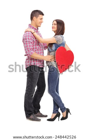 Full length portrait of a girl holding a red heart and her boyfriend isolated on white background